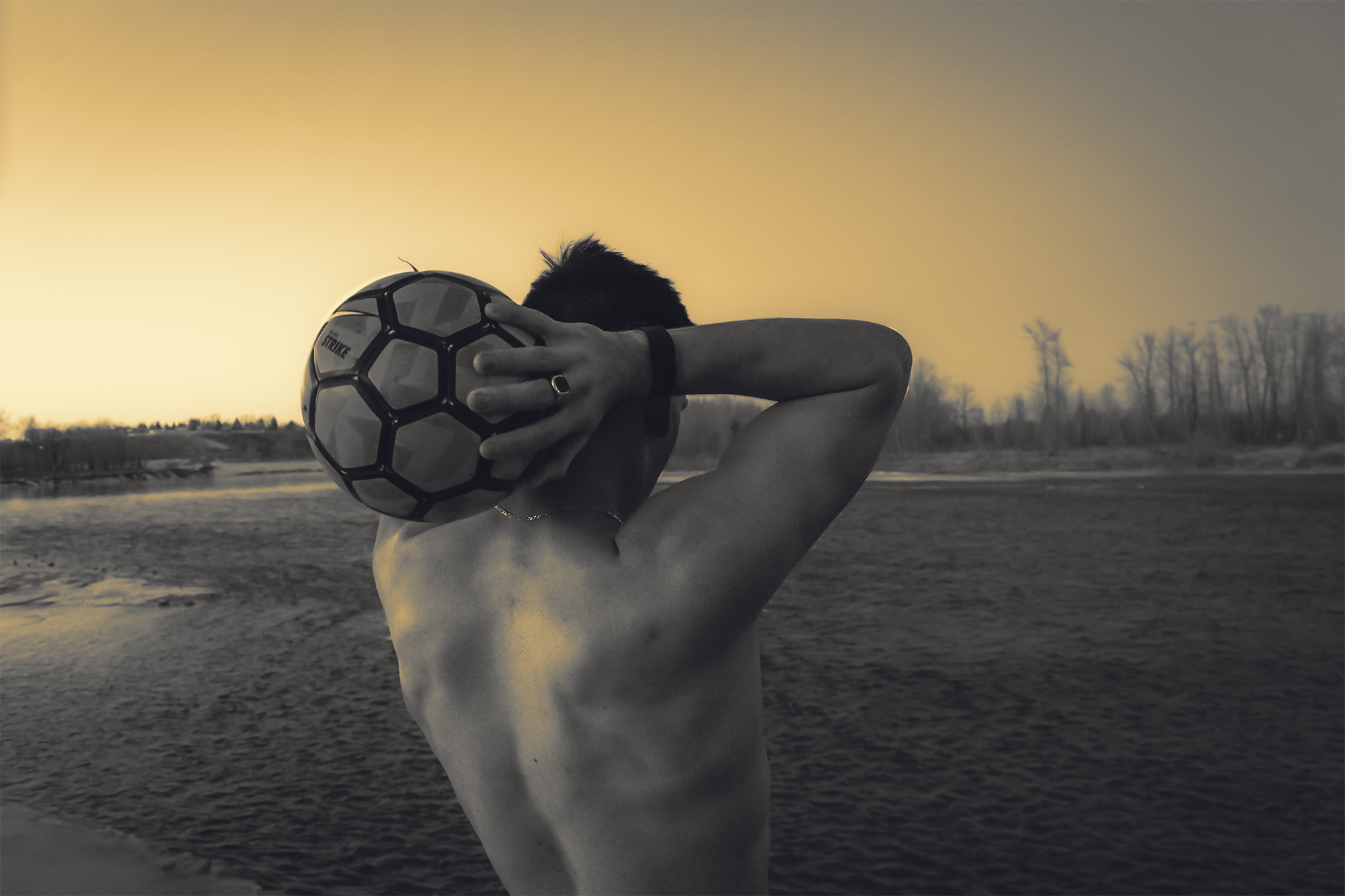 River with man throwing soccer ball